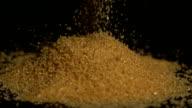 Golden Zucker gießen, auf schwarzem Hintergrund
