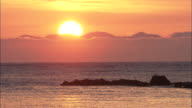 Golden sun rises above cloud and shimmers on rippling water, Shakotan Peninsula, Hokkaido