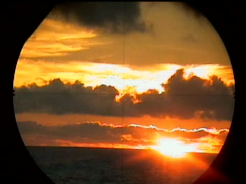 Golden sunset on horizon surrounded by orange and yellow sky with dark clouds seen through pitching periscope.