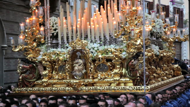 Golden Trono a religious float being carried by the Costaleros during Semana Santa, a procession through the streets of Malaga, Spain, Europe