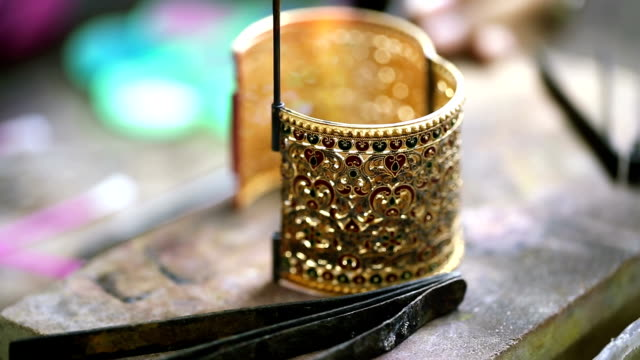Goldsmith Jeweler use gasoline burner melting and decorating bracelet