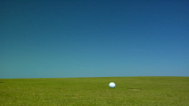 CU, Golf ball falling into hole, North Truro, Massachusetts, USA