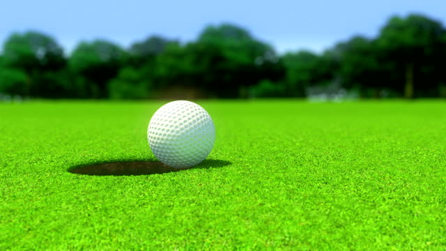 Golf ball into a hole closeup