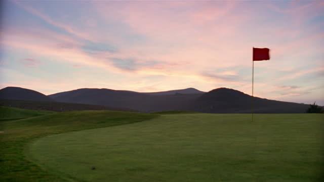 Golf ball moving towards flag on golf course