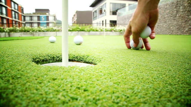 Golf ball rolls into hole