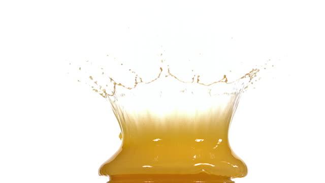 CU SLO MO Golfball falling and splashing into orange juice against white background / Vieux Pont, Normandy, France