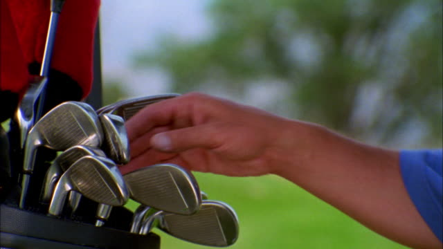 A golfer chooses a club from his bag.