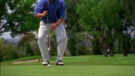 A golfer crouches behind his golf ball, then prepares to putt.