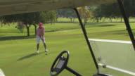 Golfer hitting ball, golf cart in foreground