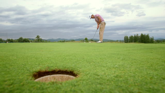 HD: Golfer schlagen den Ball in ein Loch