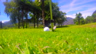 Golfer Hitting the Golf Ball on the Wet Grass