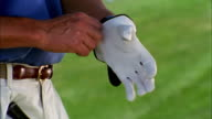 A golfer pulls on a golf glove and grips his club.