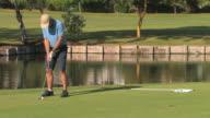 Golfer putting ball, medium shot, Spain