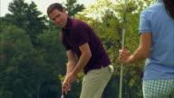 MS, Golfer putting towards woman holding flag pole, Seco, Maine, USA