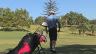 Golfer walks and takes shot, Spain