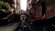 A gondola glides through a narrow canal and under a bridge in Venice.