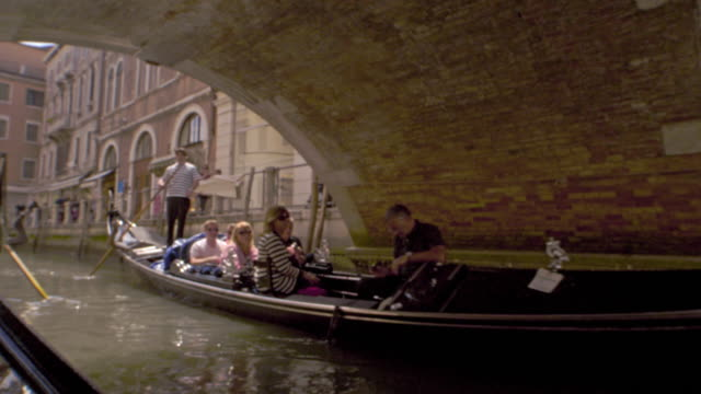 Gondolas ride under a footbridge in slow motion