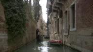 WS POV Gondolier Steers gondola down narrow canal / Venice, Veneto, Italy