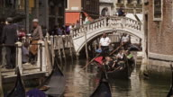 VENICE, ITALY - May 2:  Gondolier steer's gondola under a bridge on May 2, 2012 in Venice.