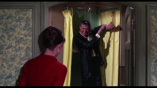 Goofy man (Cary Grant) makes woman (Audrey Hepburn) laugh by taking fully-dressed shower