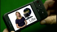 Google Android technology launches new mobile phone GRAPHICISED SEQ Hand holding mobile phone / Reporter to camera in front of videowall on mobile...