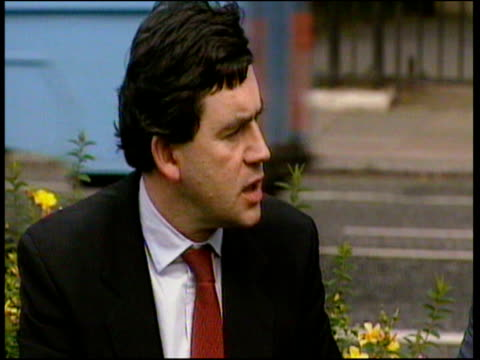 Gordon Brown and Tony Blair sitting on wall chatting before Blair became Prime Minister traffic passes in background 1992