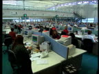 Gordon Brown's war chest of money LIB Leeds First Direct Call centre Women sitting speaking on phone headsets at call centre TRACK past desks in call...
