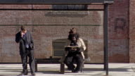 Gorilla in trenchcoat reading newspaper in bus stop / businessman talking on cell phone walking up to bus stop / traffic passing in foreground / New York City