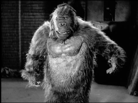 Gorilla (costume) walking near building toward camera growling