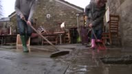 Government review into flooding condemmed as promising a 'sticking plaster' on future prevention / People sweeping muddy water down drain
