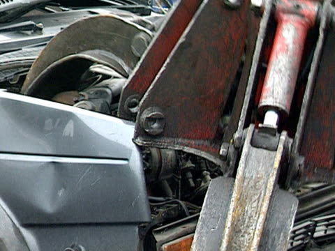 A grabber lifts the engine out of a junked car at a scrapyard 2000