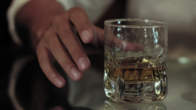 grabbing a glass with scotch bourbon single malt whiskey from a reflecting glass table