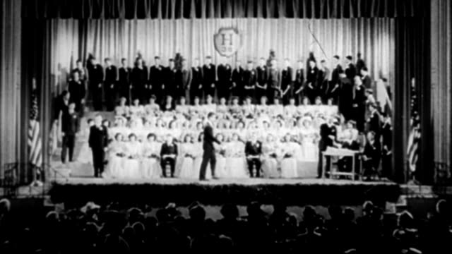 Graduates walking across stage to receive diplomas during graduation ceremony 1933