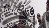 SLO MO. Graffiti artist creates intricate wall art with spray paint in white studio exhibit.