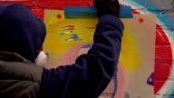 Graffiti Artist Removes Stencil from Wall