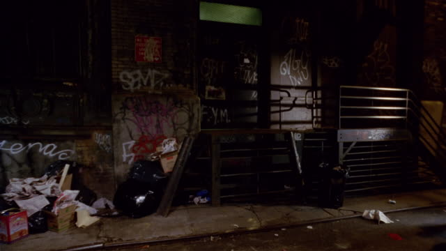 Graffiti-covered building in dark alleyway / gang members approaching two men / standing face-to-face