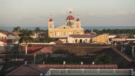 Granada - Nicaragua time lapse from sunset to night. Skyline from the vantage point of the bell tower La Merced. In this 4K video we can see tile roofs in the foreground and the colonial style Cathedral with a dome and Cocibolca lake on the background.