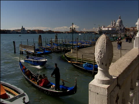 Grand Canal of Venice including gondolas small boats and life boat being rowed along canal dome of Santa Maria della Salute church in background