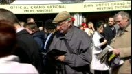 Liverpool Aintree Race Course EXT Racing punters arriving for the Grand National race and placing bets at oncourse betting stands