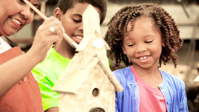 Barnbarn i workshop med aktiv senior farmor bygga birdhouses.