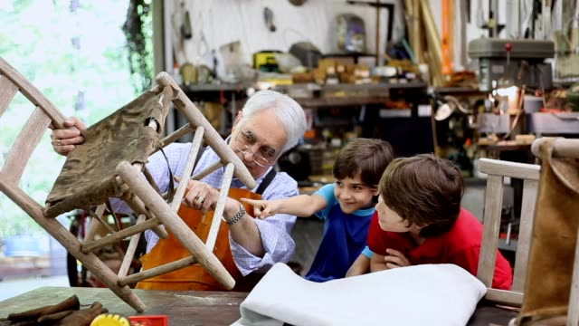 Grandchildren in workshop with grandfather reparing antique furniture.