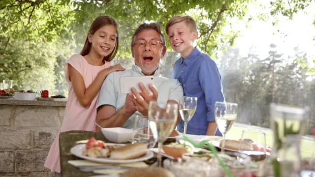 SLO MO Granddad making a selfie with his grandkids at the picnic table
