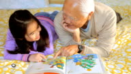 MS Granddaughter (8-9) and grandfather looking at picture book / Los Angeles, California, USA