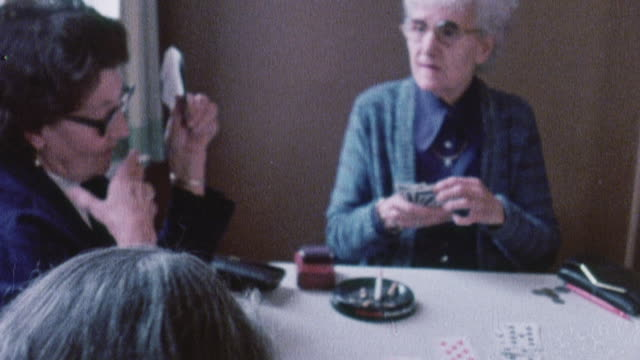 1978 MONTAGE Granddaughter calling on her grandmother while she plays cards in a seniors center / United Kingdom