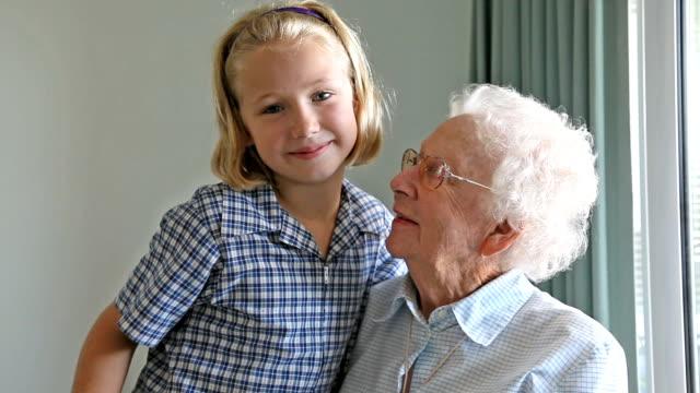Enkelin, die ihre Großmutter eine Umarmung im Haus