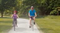 TS Enkelin Reiten Ihr Fahrrad durch den park mit Opa