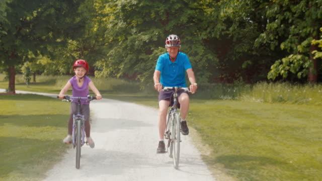 TS barnbarn ridning hennes cykel genom parken med farfar