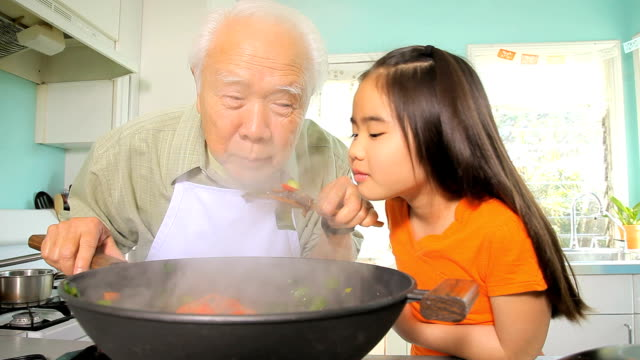 MS ZI Granddaughter (8-9) watching grandfather cooking in wok / Los Angeles, California, USA