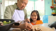 MS DS Granddaughter (8-9) watching grandfather cutting vegetables for wok / Los Angeles, California, USA