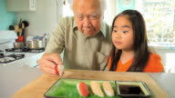 MS DS Granddaughter (8-9) watching grandfather putting last piece of sushi on plate / Los Angeles, California, USA